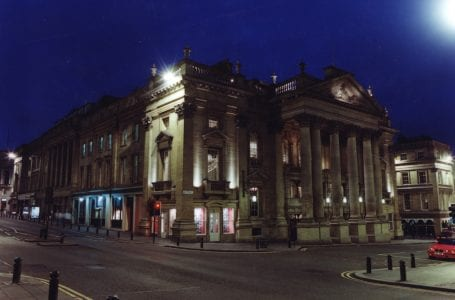 Type : Photograph Medium : Print-colour Description : A photograph of the Theatre Royal Grey Street Newcastle upon Tyne taken in the 1990s.  The view is of the front and the side on Market Street.  It is night-time and the theatre is lit up.The Theatre Royal was built 1836-37. The architects were John