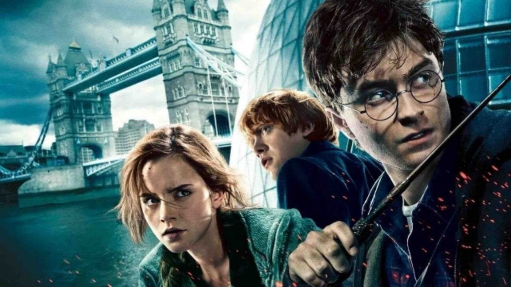 Two boys, one holding a wand, and a girl are in front of Tower bridge in London, all looking dramatically away from the camera