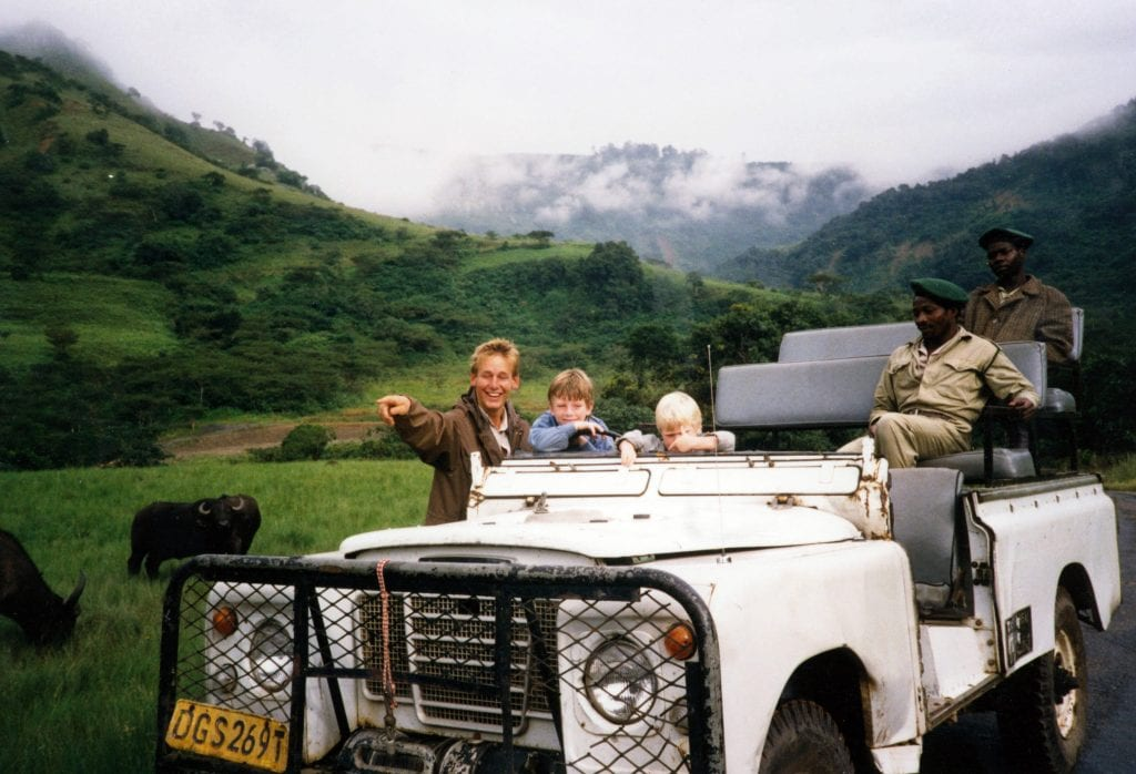 One white adult man (James Meyer) and two young boys (Peter and Jamie) standing behind white truck occupied by two Black adult men in uniform. Two buffalo stand behind them, and there is an expanse of green hills, trees and heavy mist in the background