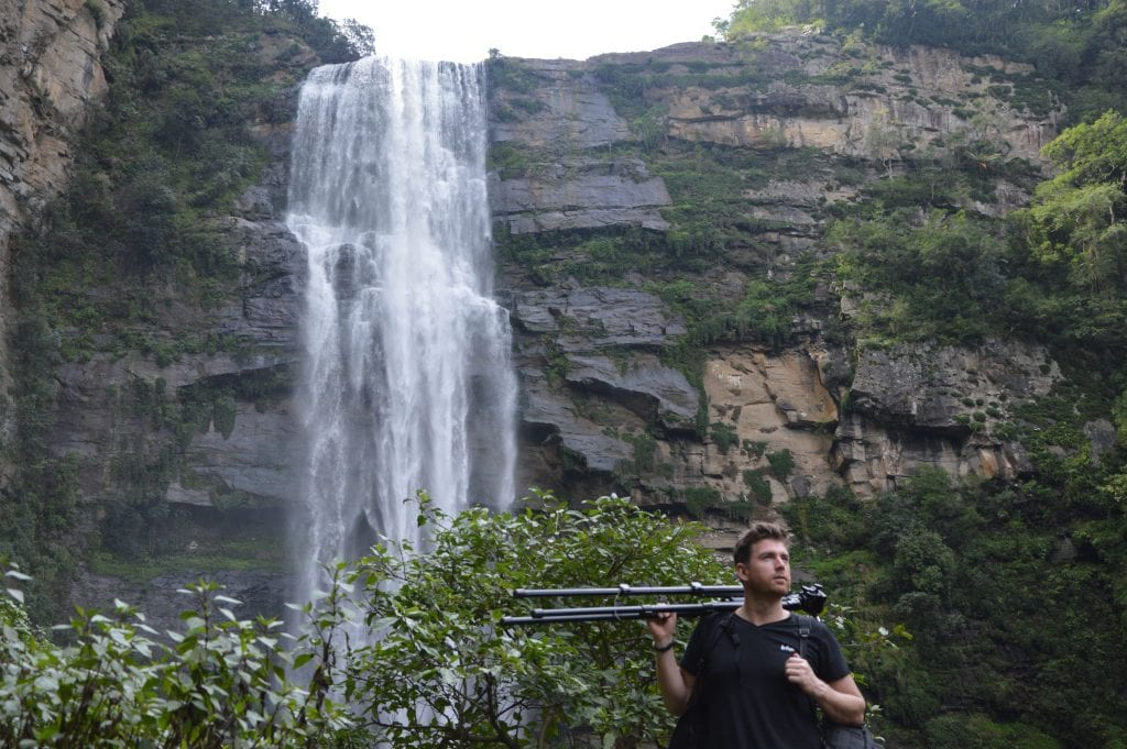 Meyer, brown hair and black t-shirt, with a tripod held over shoulder with right hand, standing in front of lush green vegetation with a large waterfall in the background.